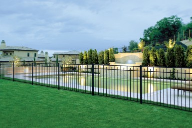 A well-manicured lawn, bordering a pool deck that is protected by beautiful metal fencing.